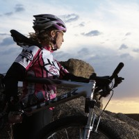 Female biker watching sunset, side view